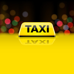Yellow taxi car roof sign at night