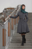 Beautiful stylish woman  in grey coat standing on stairs