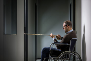 Conceptual photo of man on wheelchair is pulling a rope symboliz