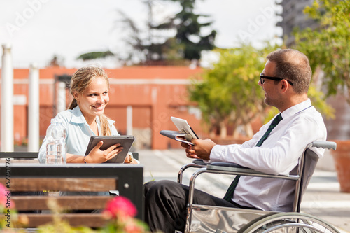 Businessman on wheelchair talks to his colleague