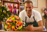 Smiling florist next to a coloful bouquet