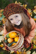 Little girl with autumn pumpkins in a basket