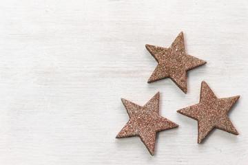 Braune Sternchen auf weißem Holz