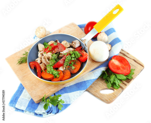 Sliced fresh vegetables in pan on wooden board isolated on