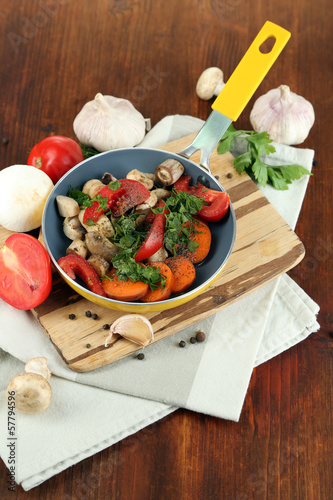 Sliced fresh vegetables in pan on wooden table close-up