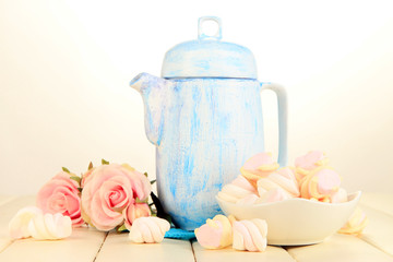 Antique white teapot on wooden table on white background