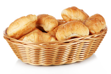 Tasty croissants in wicker basket isolated on white