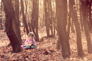 Little girl reading book in autumn forest