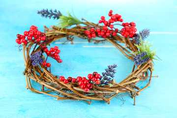 Wreath of dry branches with flowers on wooden table close-up