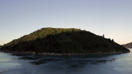Sunlit island passing by, tracking view from a ferry