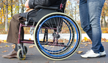 Disabled man in a wheelchair with a carer