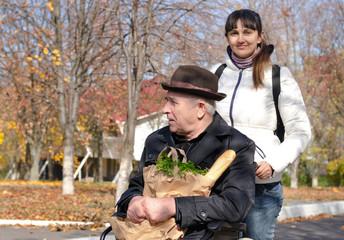 Woman taking an elderly disabled man shopping