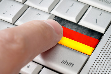 Business concept male finger pressing German enter key