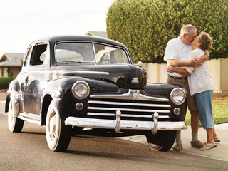 senior couple with vintage car kissing