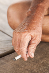 Hand of an old man holding a cigarette