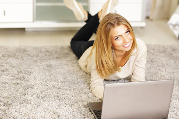 Happy young woman with laptop lying on the carpet at home