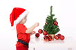 little cute boy with Santa hat decorates christmas tree