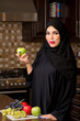 Arabian woman holding an apple in the kitchen