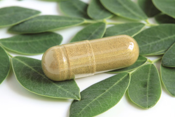 Moringa oleifera capsule with green fresh leaves on white backgr