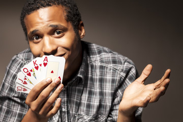 young man with compassion holds the winning poker cards