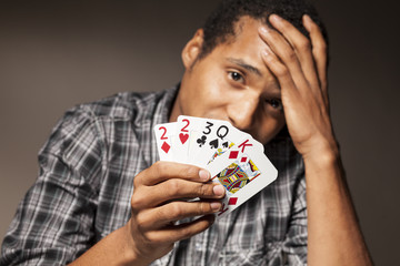 young dark-skinned man shows bad poker cards