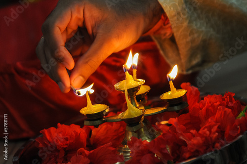 diwali festival of lights , hand lighting an indian oil lamp