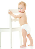 baby holds on to a white chair. isolated.