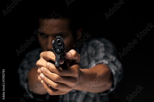 dark-skinned young man aiming with his gun at you