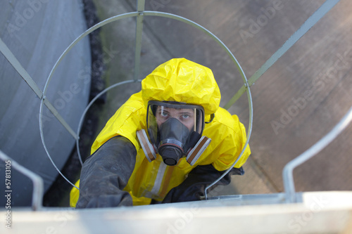 technician in protective uniform going up a metal ladder