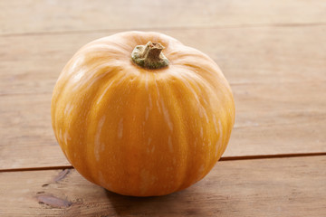 Whole raw pumpkin on wooden table