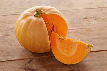 Open raw pumpkin on wooden table