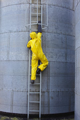 specialist in  uniform going up a metal ladder on storage tank