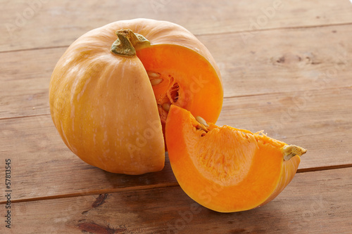 Open raw pumpkin on wooden table