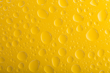 Clear yellow water drops over yellow background