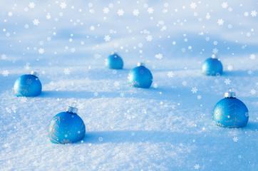 Blue Christmas balls on snow field.