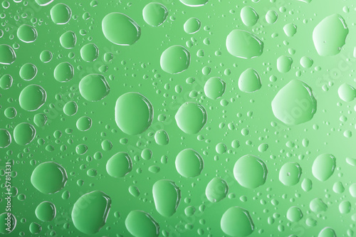 Clear green water drops over green background