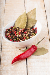 Mixed pepper in can on wooden background