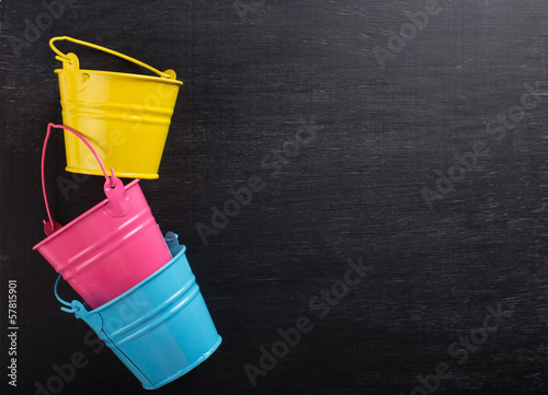 Small decorative buckets on wooden background
