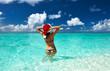 Woman in santa's hat at beach