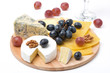 assorted cheeses, grapes and glass of wine on board, isolated