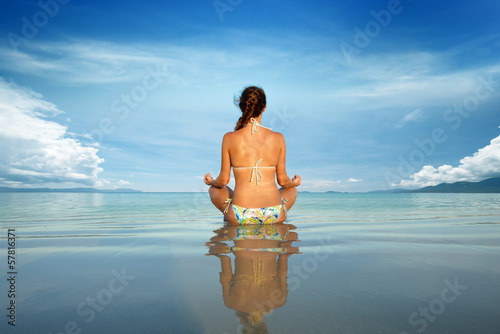 Young beautiful woman in a lotus position on a background of blu