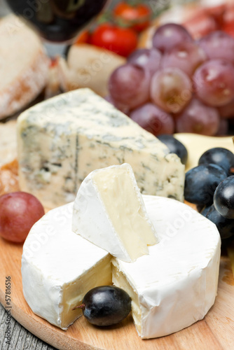 Camembert, blue cheese, grapes and walnuts on wooden board