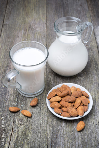 Jug and glass cup with almond milk on a wooden table