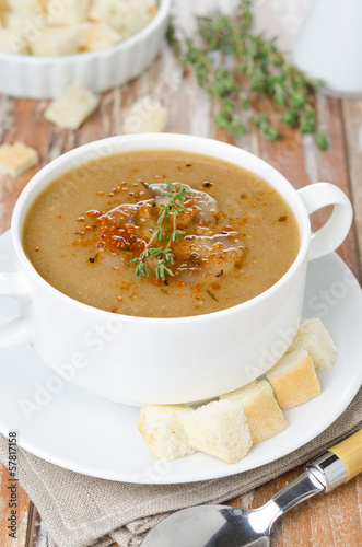 Mushroom cream soup with croutons and thyme in a bowl vertical