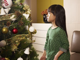little asian girl sits next to christmas tree