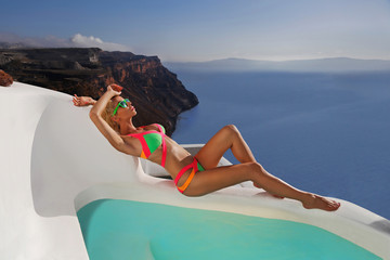 beautiful woman in the pool in a swimsuit in santorini