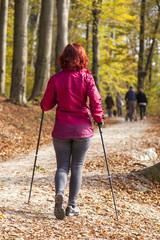 Sportive cute woman Nordic walking autumn cross country