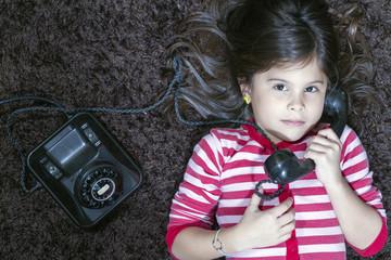 Niña en pijama mira seriamente mientras conversa por teléfono