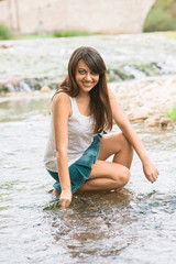 Young girl walks around the bed of a river Wetting his feet