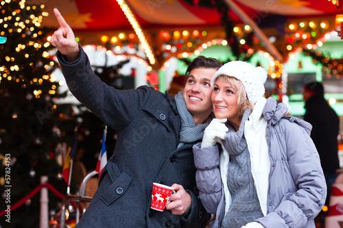 Pärchen trinkt Glühwein auf Weihnachtsmarkt im Advent